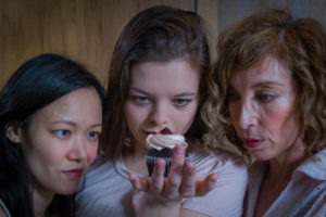 Photo by Ron Diamond of three actors fixing their gazes on a cupcake in I'm Not Here